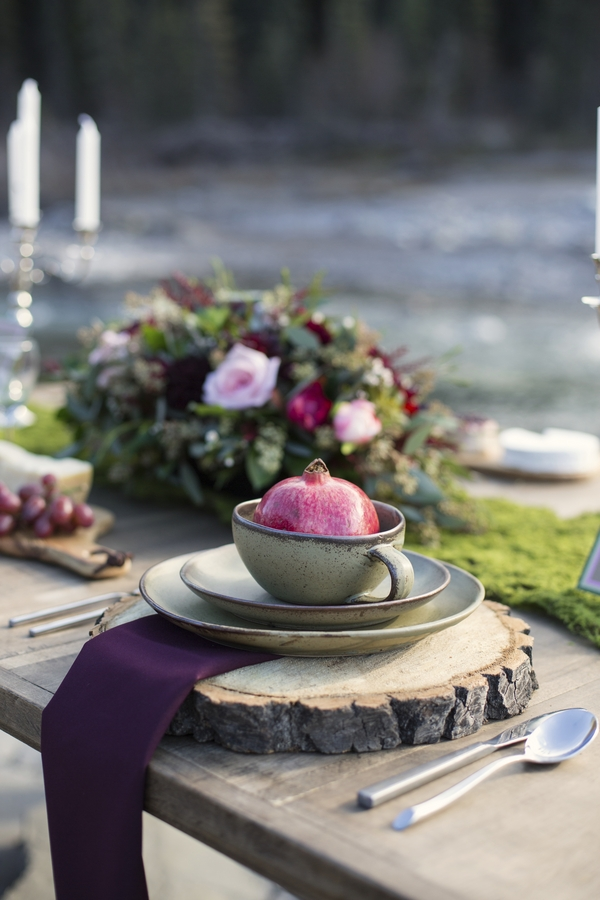 Pomegranate plate centerpiece on rustic wood slabs